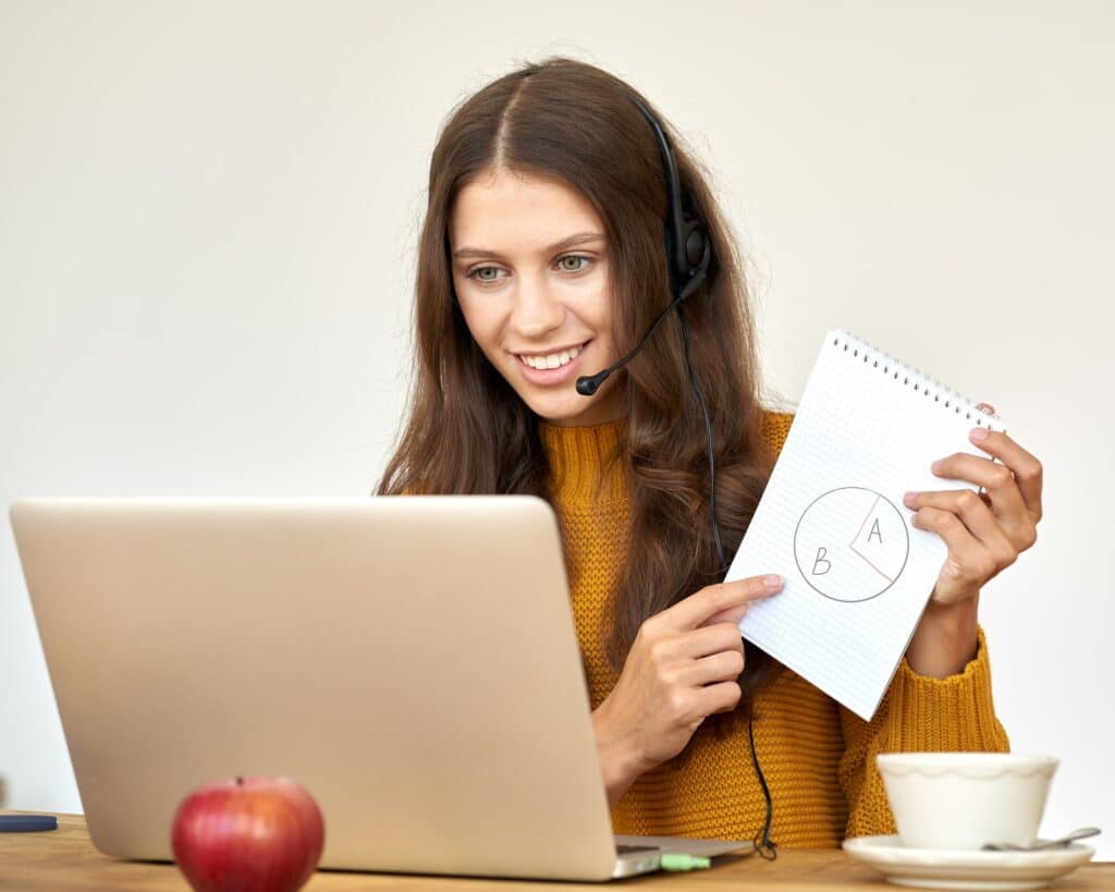 Happy woman in headset speaking by conference call and video chat on laptop in office